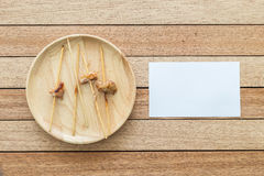 Empty bamboo stick of grilled pork and paper note on wooden dish Stock Photos