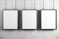 Empty banners on brick wall. Empty rectangular banners hanging on white brick wall background. Gallery, advertising, exhibition concept. Mock up, 3D Rendering Royalty Free Stock Photography
