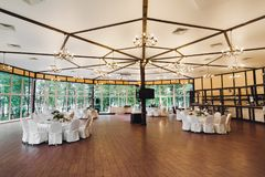 An empty banquet hall. Big white ceiling, tables and chairs for a large number of guests. stock image