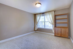 Empty basement room with wooden cabinet and beige carpet. Royalty Free Stock Photos