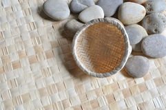 Empty basket on pebbles. An empty small basket rests on a mat with pebbles Royalty Free Stock Photography