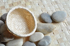 Empty basket on pebbles. An empty small basket rests on a mat with pebbles Royalty Free Stock Photos