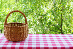 Empty basket on the table with checkered table cloth on a background of green trees. Royalty Free Stock Photos