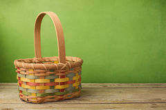 Empty basket on wooden table over grunge green background Royalty Free Stock Photography