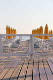 Empty bathing establishment, early in the morning. The soft colours of some umbrellas and chairs, in a bathing establishment, with a  fence in the foreground, at Royalty Free Stock Photo