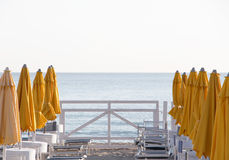 Empty bathing establishment, at sunset. The soft colours of some umbrellas and chairs, in a bathing establishment, with a  fence on the background, at the beach Royalty Free Stock Images