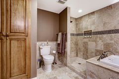 Empty bathroom interior. Light brown tile, bath tub and toilet. Empty bathroom interior. Light brown tile, bath tub, shower and toilet royalty free stock photography