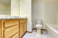 Empty bathroom. Wooden cabinet with granite top. Empty bathroom interior. Light brown cabinet with granite top, bath tub and toilet Stock Photography