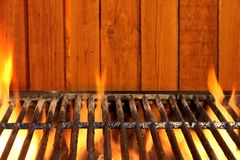 Empty BBQ Flaming Grill And Wood Wall In The Background Royalty Free Stock Photography