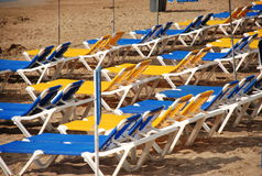 Empty beach. With blue and yellow sun chairs royalty free stock photography
