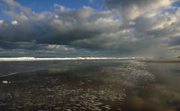 Empty beach. Deserted beach with waves and clouds royalty free stock images