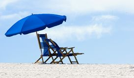 Empty Beach 2. Empty  chairs on a white sand beach with a cloud filled sky Stock Photo