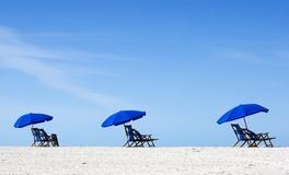 Empty Beach. Empty  chairs wiyh umbrellas on a white sand beach with a cloud filled sky Stock Images