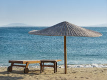 Empty beach. Deck chair and parasol on an empty beach with blue sea in the background Royalty Free Stock Photos