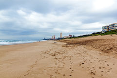 Empty Beach Against Cty Buildings and Overcast gloomy Skyline Stock Image