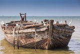 Empty beach, ancient boat in the sea Stock Photos