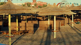Empty beach area. Panning shot of empty beach area with straw sun umbrellas. Focus on the sea at the end stock footage