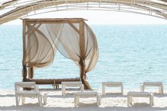 Empty beach beds. Lounge chaise on a sand shore,sun umbrellas omission, empty beach, summer.  stock photo