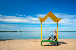 Empty beach with a bench with a canopy on the coast Stock Image