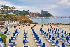 Empty beach with blue chaise longues and calm sea water with ol. D castle in background in Lerici, Liguria, Italy stock image
