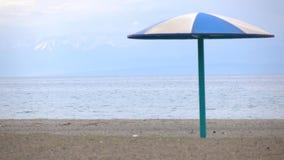 Empty beach and blue sun umbrella against snow peaks. 4K low season video. Empty beach and blue sun umbrella against snow peaks. 4K low season shot stock footage