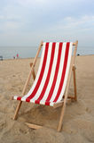 Empty beach chair. An empty red/white wooden beach chair at the beach Stock Photo