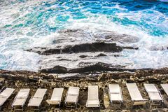 Empty beach chair deckchairs sunloungers on cliff rocks stormy sea Royalty Free Stock Image