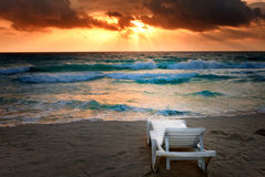 Empty beach chair before sea. Bright sunset, waves Stock Image
