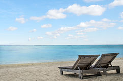 Empty beach chairs on empty tropical beach Royalty Free Stock Photography