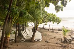 Empty beach chairs are lined up in the wind and rain. Tropical Storm Nate turns the waters of the Pacific red from storm run off. Tropical Storm Nate turns the royalty free stock photos