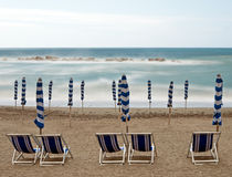 Empty beach with chairs, rocks and silky sea. Deserted. Royalty Free Stock Images