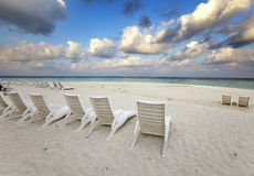 Empty beach chairs on sand by the sea at sunrise Stock Photo