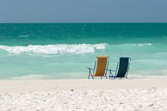 Empty Beach Chairs In The Surf. A pair of empty beach chairs at the water's edge on the Treasure Island, Florida public beach Royalty Free Stock Images