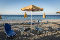 Empty beach with deckchairs and a yellow parasol Stock Photo