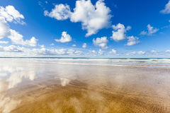 Empty Beach in Devon, England. Empty beach with fluffy clouds reflected in the wet sand, Saunton Sands in North Devon, UK Stock Images