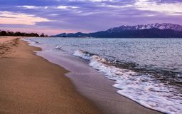 Empty beach in the evening - waves crashing on the sand royalty free stock photography