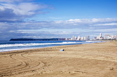 Empty Beach and Litter Bin Against City Skyline Stock Image