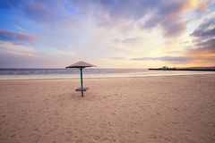 Empty beach with lonely umbrella at sunset Royalty Free Stock Image