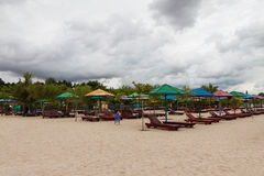 Empty beach with lots of sun loungers and umbrellas, against the Stock Photography