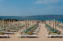 An empty beach with lounge chairs & umbrellas. An empty beach with umbrellas & lounge chairs Stock Image
