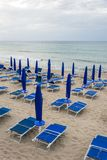 Empty beach loungers on deserted beach in low season. With cloudy weather royalty free stock photo