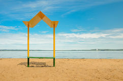 Empty beach with a bench with a canopy on the coast Stock Photos