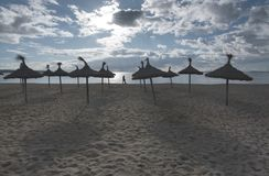 Empty beach with parasols. In Palma de Mallorca on a sunny day in November in Mallorca, Balearic islands, Spain Royalty Free Stock Photography