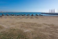 Empty beach with parasols. In Palma de Mallorca on a sunny day in November in Mallorca, Balearic islands, Spain Royalty Free Stock Photos