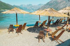 Empty beach with sun loungers and umbrellas. sea with mountains. Summer vacation stock photography