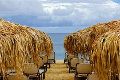 Empty beach with sunshades and chairs. On a sunny day before rain Royalty Free Stock Images