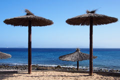 Empty beach with thatched-roof umbrellas Royalty Free Stock Images