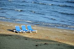 Empty beach with three sun loungers on sand stock image
