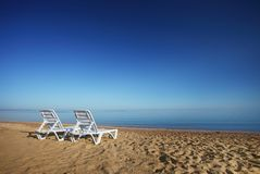 Empty beach with two sunchairs Royalty Free Stock Photos