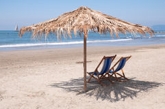 Empty beach waiting for summer. An empty beach with two beach chairs under a beach umbrella Stock Photography